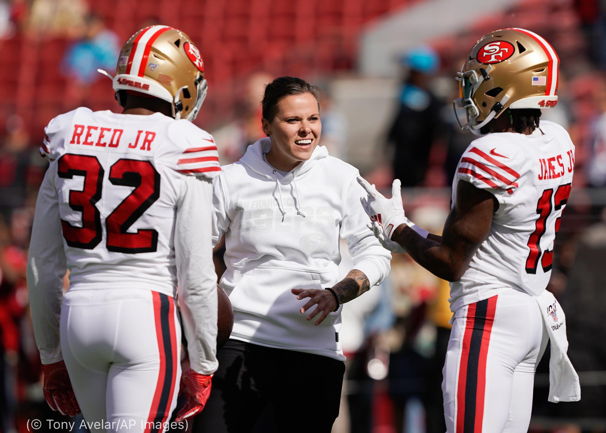 مربی زن فوتبال آمریکایی با دو بازیکن صحبت می کند (© Tony Avelar/AP Images)