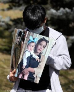 Seorang laki-laki menundukkan kepala sambil memegang foto (© Burhan Ozbilici/AP Images)