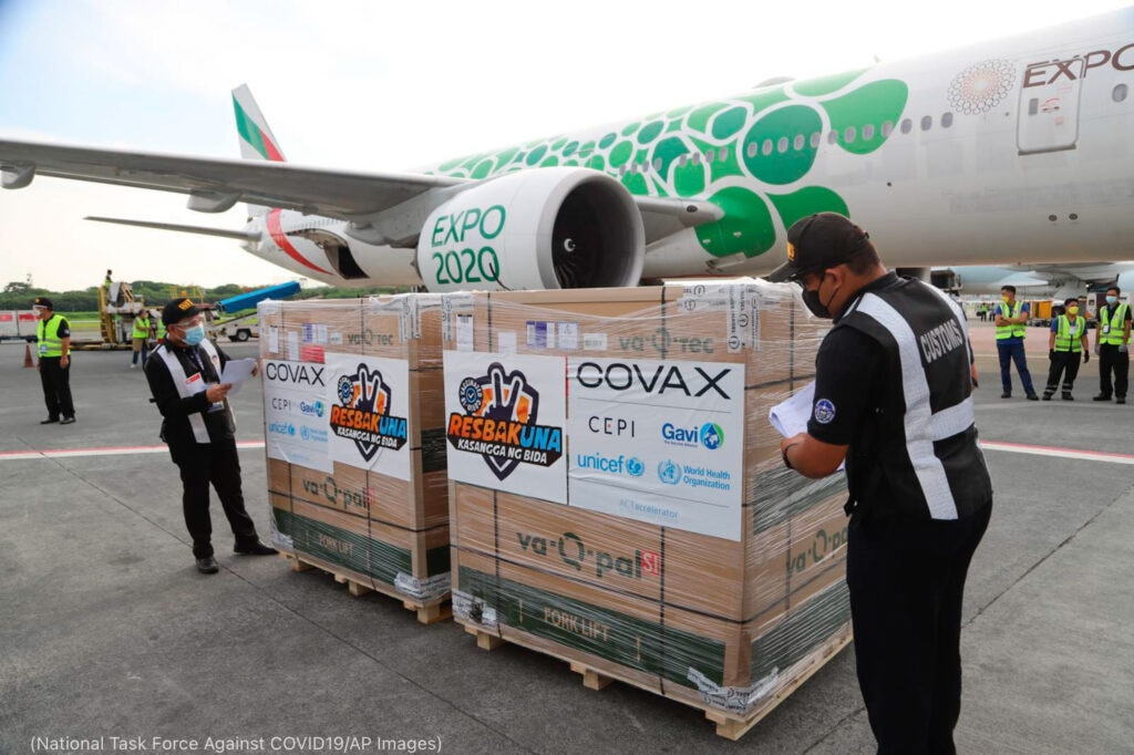男子在飞机前检查货架板上的疫苗包装箱 (National Task Force Against COVID19/AP Images)