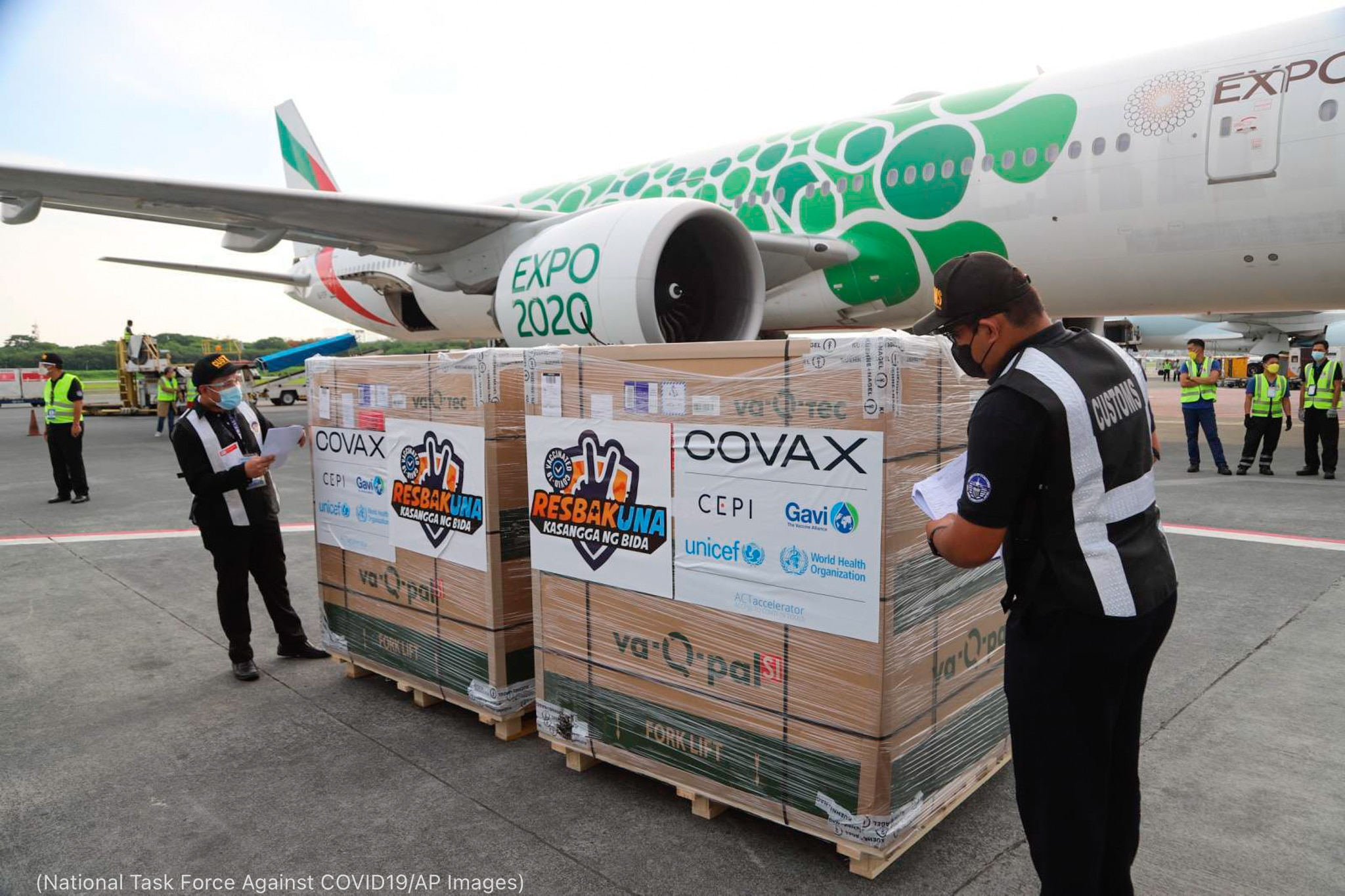 Hombres delante de un avión inspeccionando un palé de cajas de vacunas (National Task Force Against COVID19 [Grupo Nacional de Trabajo contra COVID19]/AP Images)