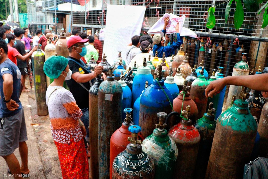 Pessoas se reunindo em torno de tanques de oxigênio (© AP Images)