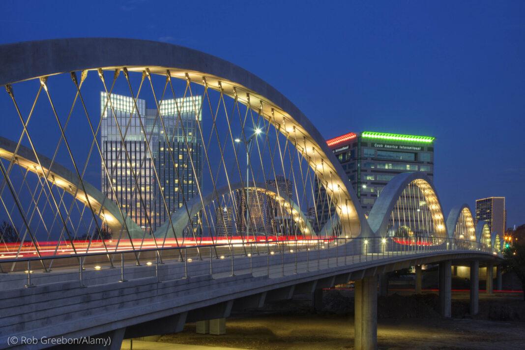 Vista noturna de arranha-céus de cidade com ponte em primeiro plano (© Rob Greebon/Alamy)