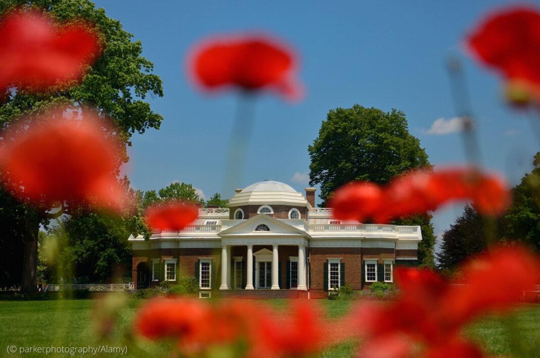 Bangunan batu bata dengan tiang putih dan kubah di balik bunga-bunga merah (© parkerphotography/Alamy)