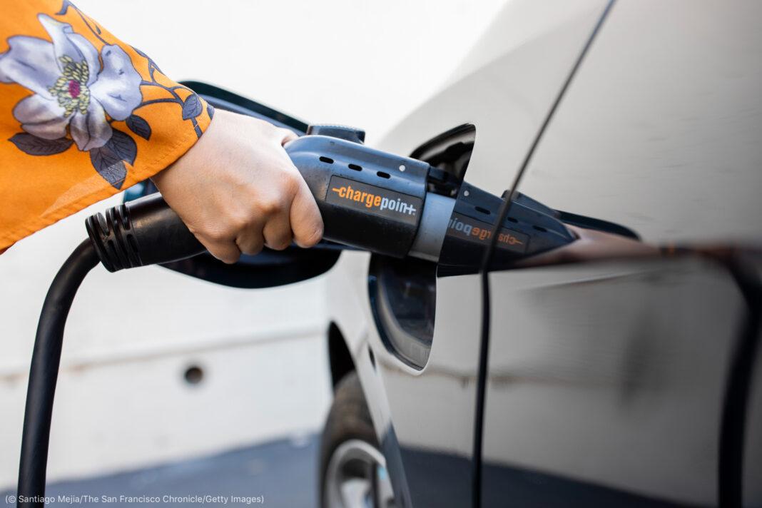Tangan perempuan memasukkan kabel pengisi daya ke mobil listrik (© Santiago Mejia/The San Francisco Chronicle/Getty Images)