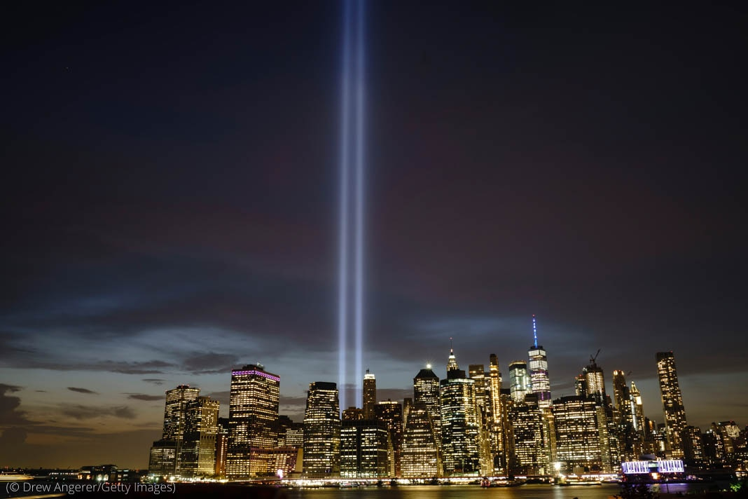 2 light beams reaching up to the sky out of the New York City skyline (© Drew Angerer/Getty Images)