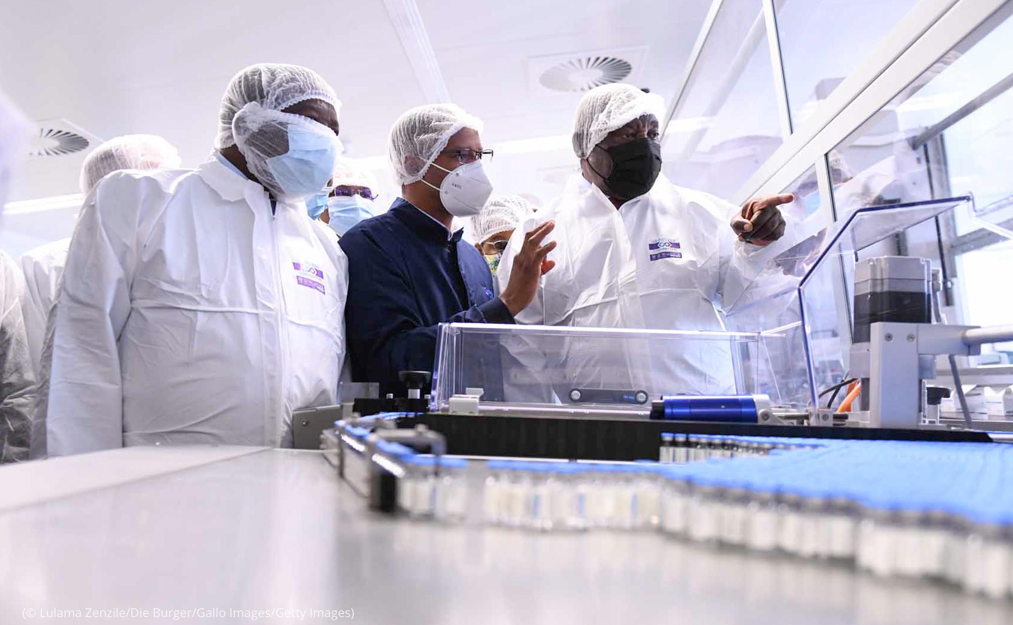 رجال يرتدون سترات واقية ينظرون إلى آلة وقوارير أدوية (© Lulama Zenzile/Die Burger/Gallo Images/Getty Images)