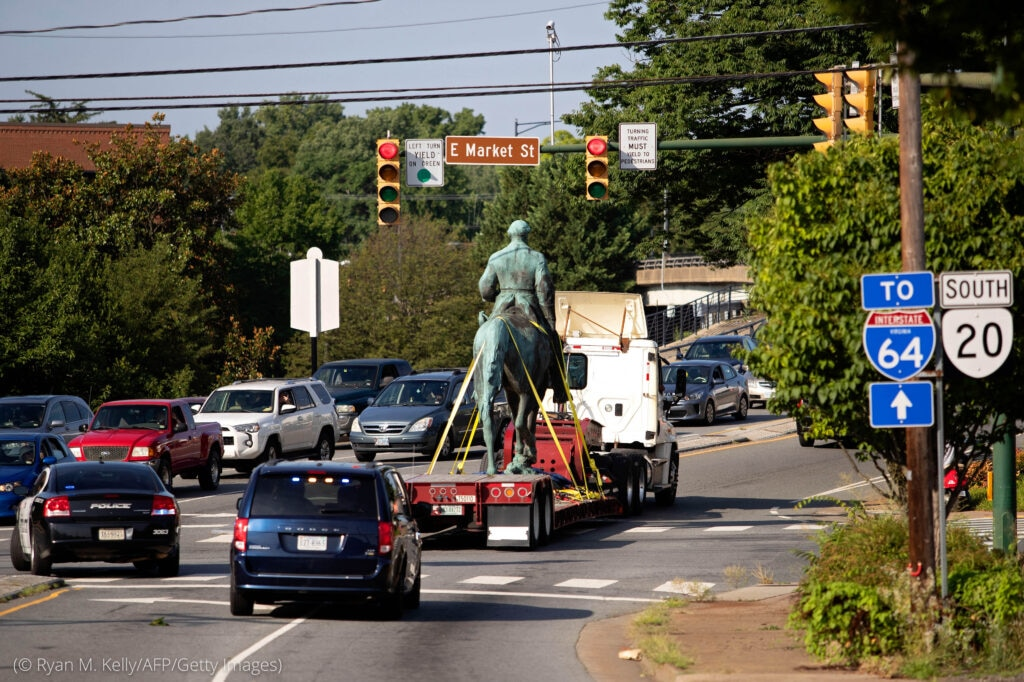 Statue of man on horseback being driven on flatbed truck in traffic (© Ryan M. Kelly/AFP/Getty Images)
