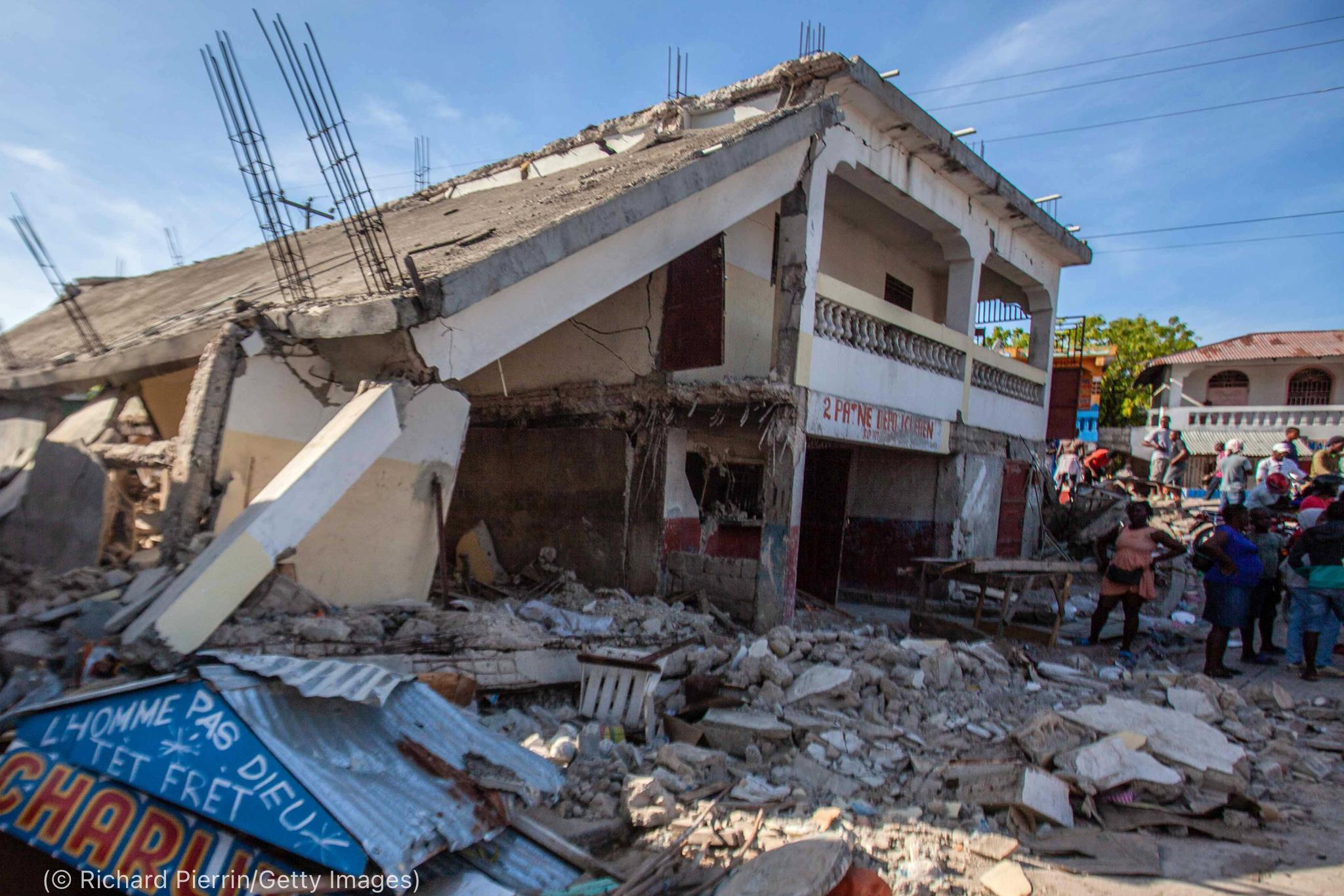 Personas mirando escombros de un edificio (© Richard Pierrin/Getty Images)