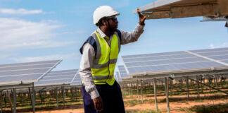 Homem examinando painéis solares (© Isaac Kasamani/AFP/Getty Images)