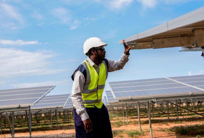رجل ينظر إلى ألواح شمسية (© Isaac Kasamani/AFP/Getty Images)