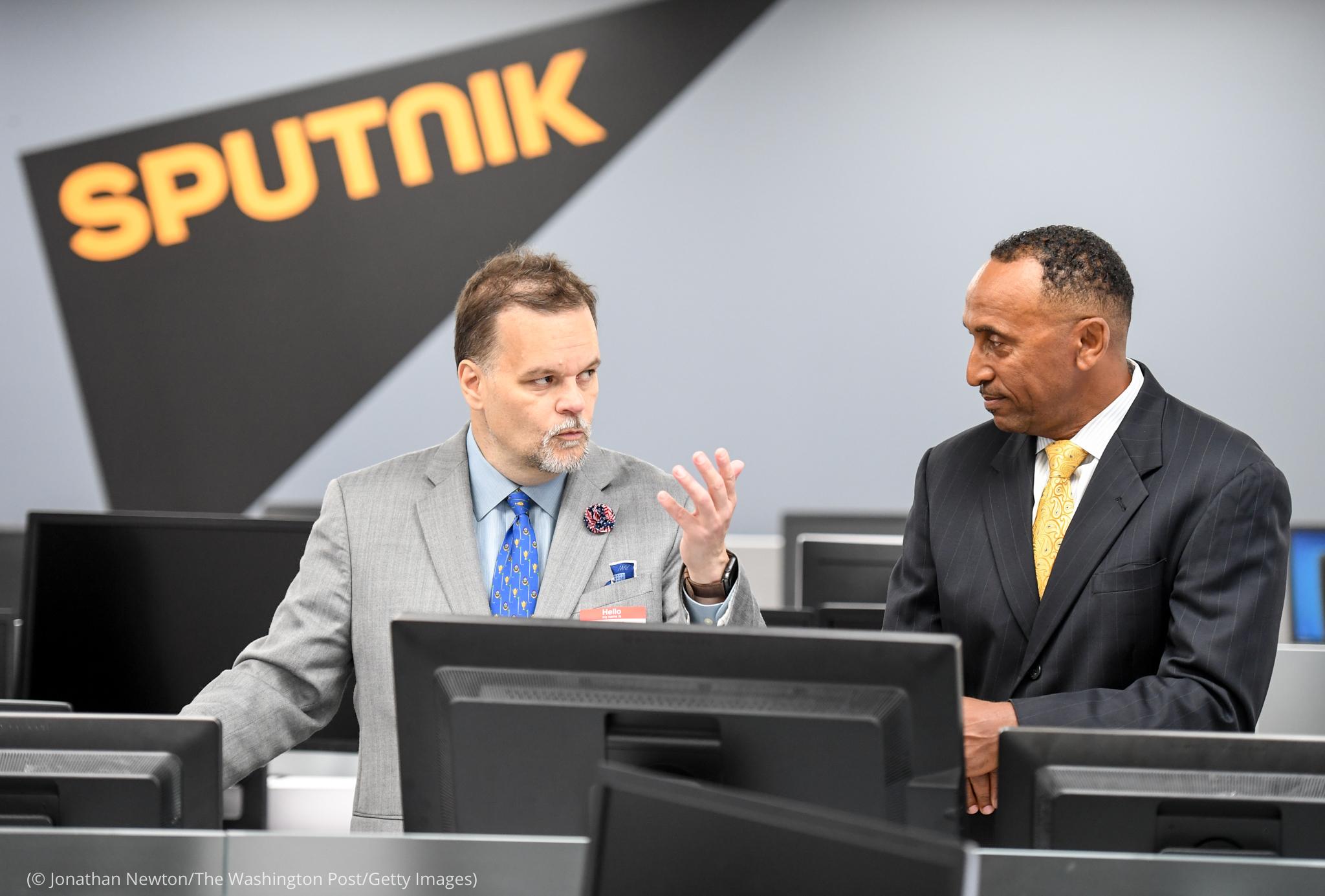 Deux hommes tenant une discussion sous un panneau avec le mot « Sputnik » au mur derrière eux (© Jonathan Newton/The Washington Post/Getty Images)
