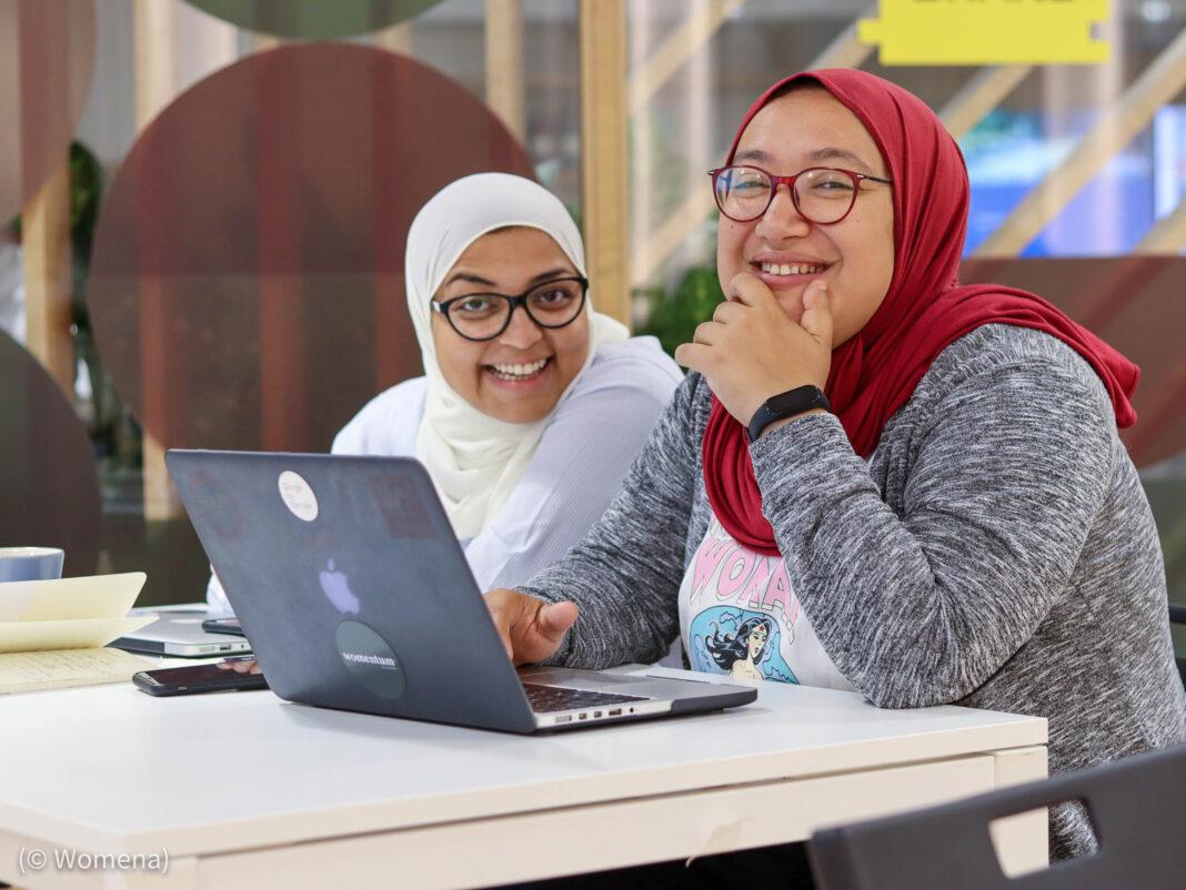 Rasha Rady e Doaa Aref com hijab sentadas trabalhando em um laptop em uma mesa (© Womena)