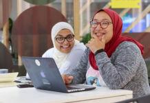 Rasha Rady and Doaa Aref in hijabs seated at laptop on table (©Womena)