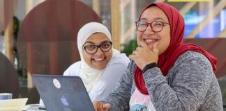 راشا رادی و دعا عارف با حجاب جلوی لپ تاپ روی میز نشسته اند. (© Womena)