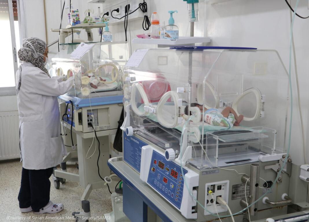 Perempuan memeriksa bayi di inkubator (Courtesy of Syrian American Medical Society/SAMS)