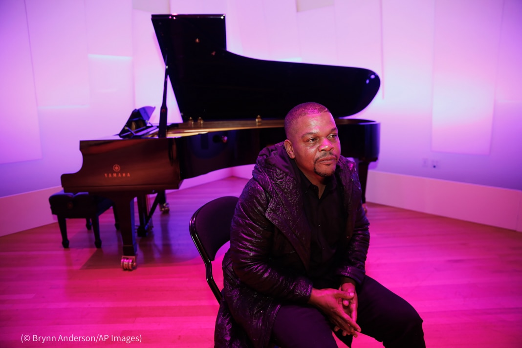 Man sitting in front of piano (© Brynn Anderson/AP Images)