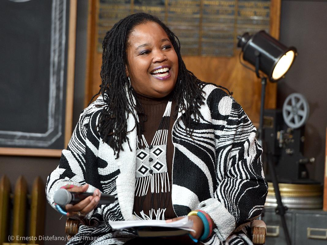 Mujer sonríe y sostiene un micrófono (© Ernesto Distefano/Getty Images)