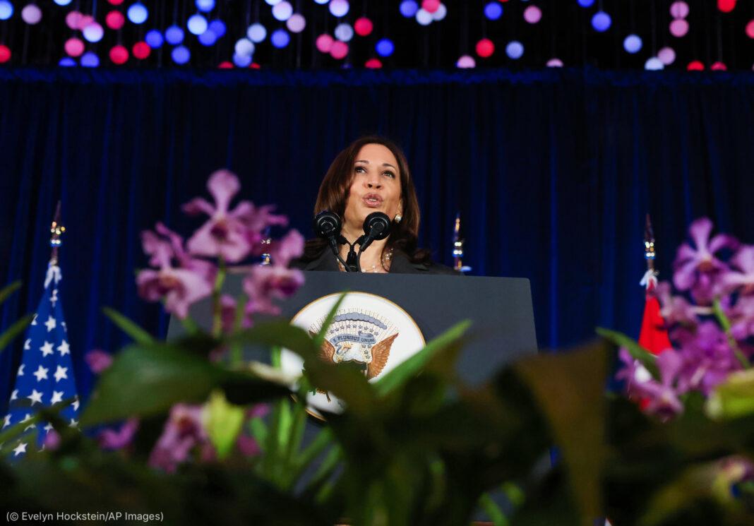 کملا ہیرس سٹیج پر کھڑی ہیں اور اُن کے گرد پھول اور رنگین روشنیاں دکھائی دے رہی ہیں۔ (© Evelyn Hockstein/AP Images)