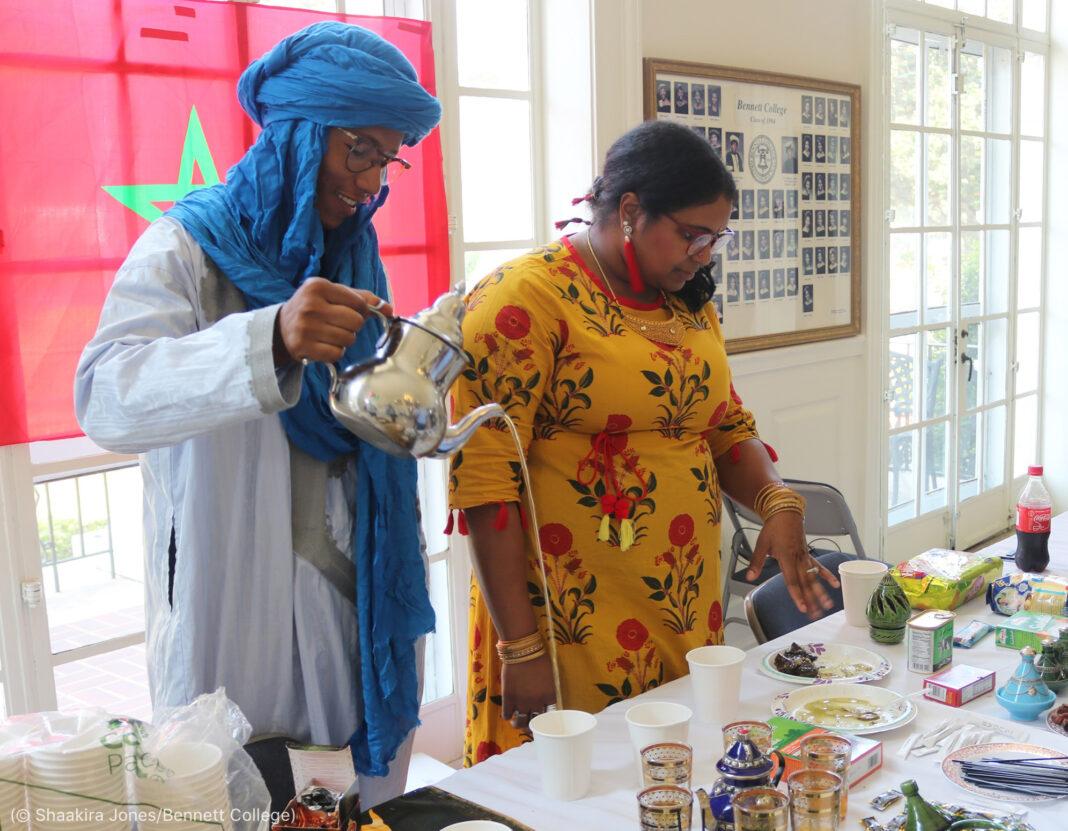 Sofyan Essarraoui pouring mint tea next to woman (© Shaakira Jones/Bennett College)