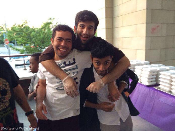 Tres jóvenes posando y sonriendo abrazados (Foto cedida por Waqas Idrees)