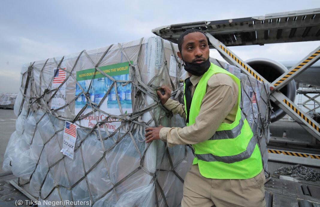Seorang laki-laki menurunkan palet bermuatan banyak kotak (© Tiksa Negeri/Reuters