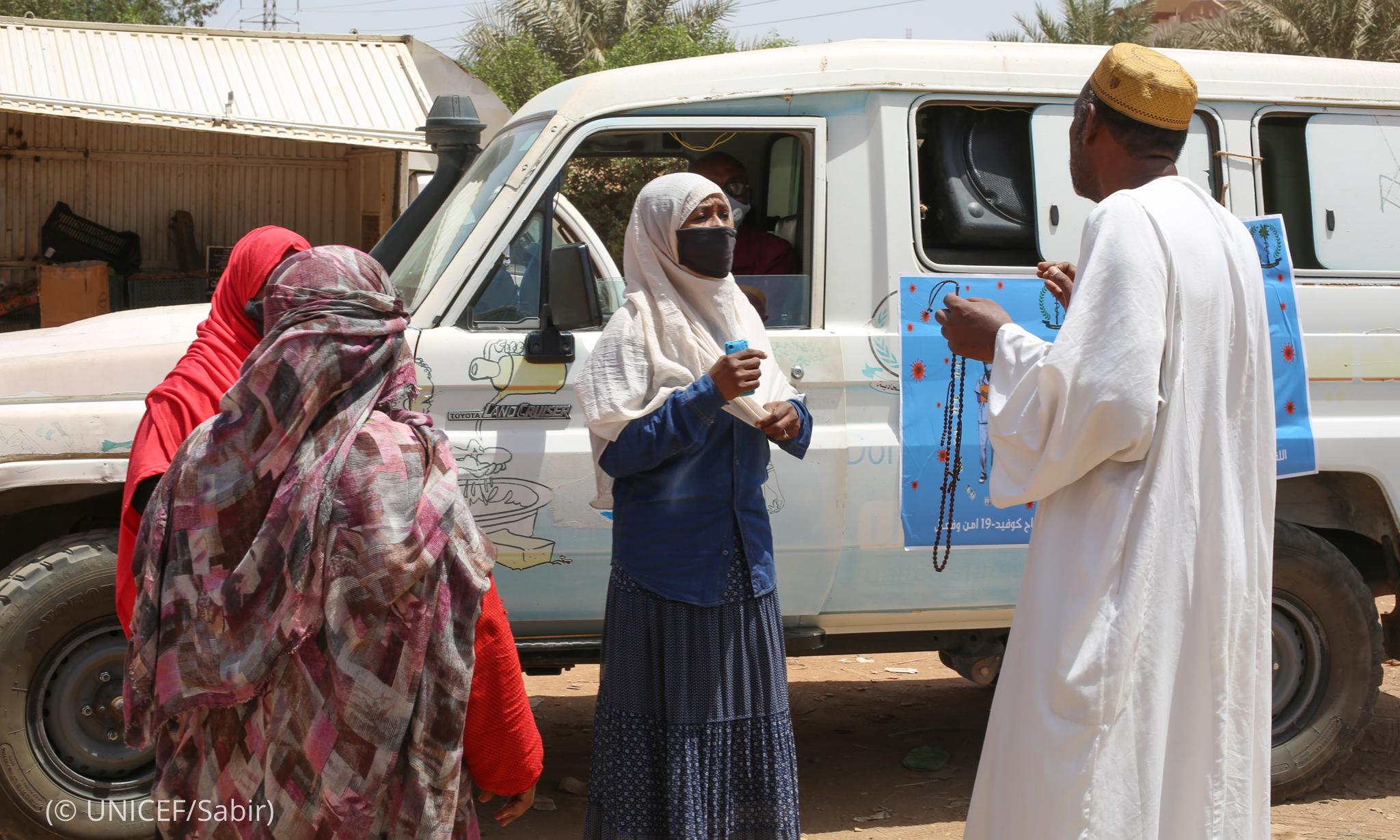 Personas hablando delante de una furgoneta (© UNICEF/Sabir)