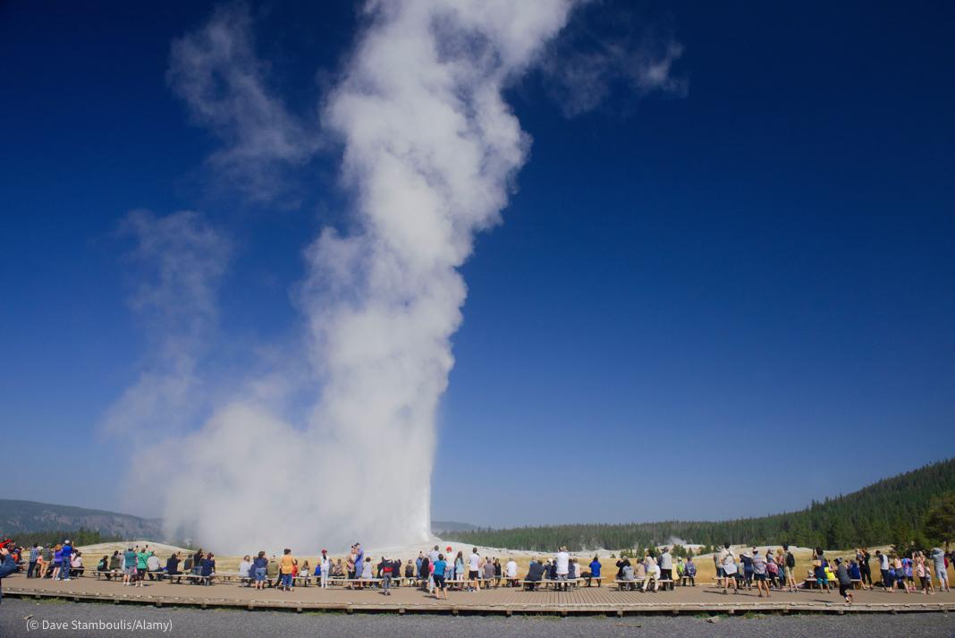 Sederetan orang menyaksikan erupsi geiser (© Dave Stamboulis/Alamy)