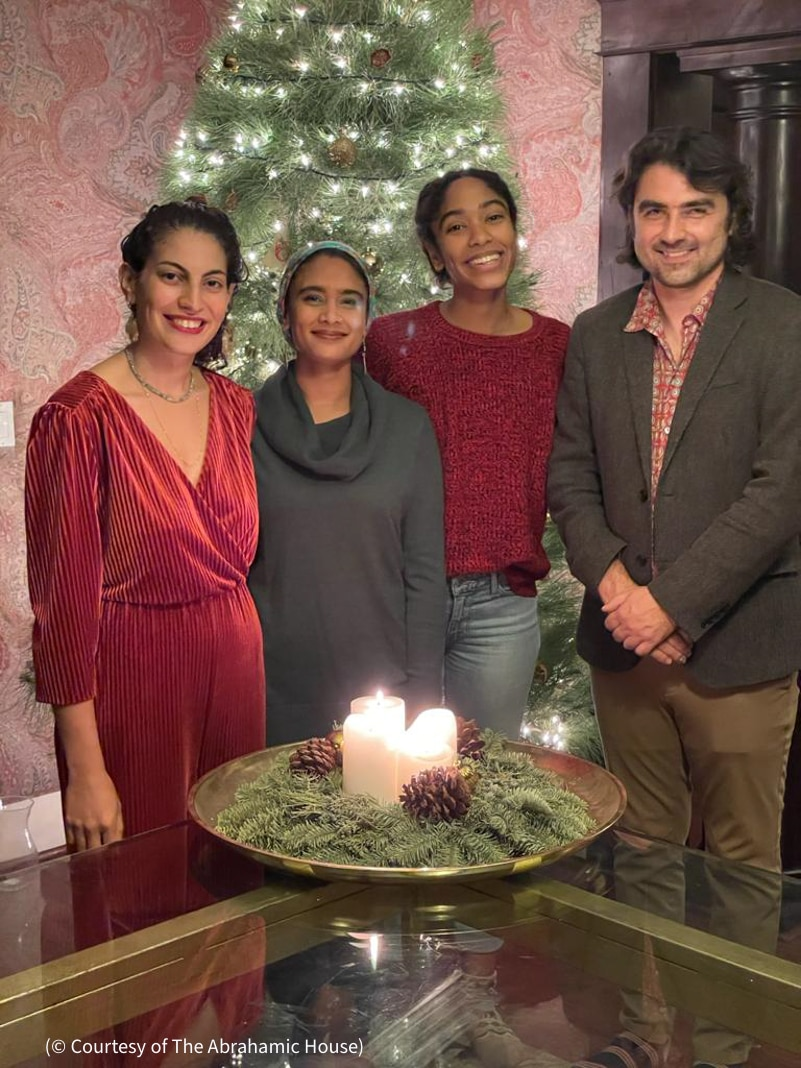 Three women and one man standing in front of Christmas tree and behind candles surrounded by pine cones and fronds (© Courtesy of The Abrahamic House)