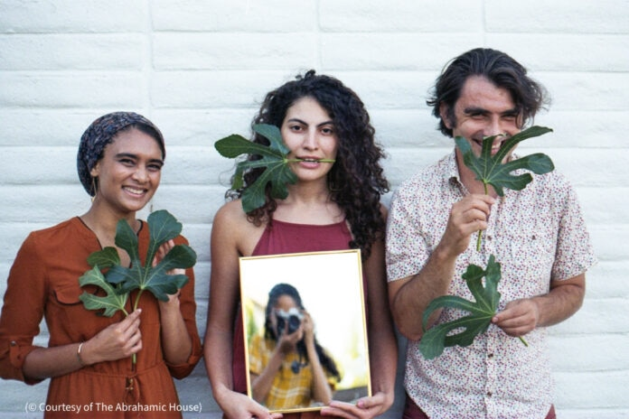 Three people against a wall for photo opp with green fronds (© Courtesy of The Abrahamic House)