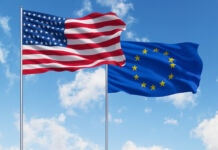 U.S. and European Union flags flying against sky (© Shutterstock)