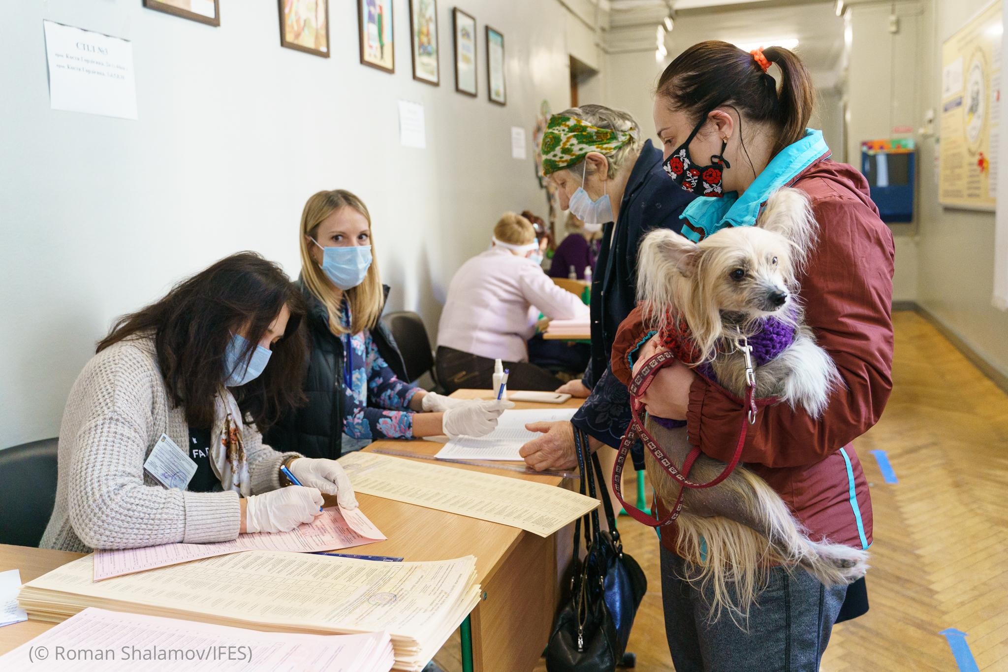 Mujer con mascarilla de pie y sosteniendo un perro frente a una mesa con otras mujeres (© Roman Shalamov/IFES)