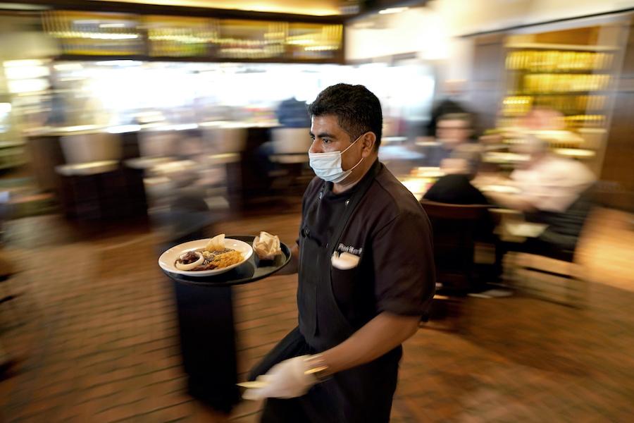 休士顿一家餐馆服务员正给顾客送餐(照片:美联社)