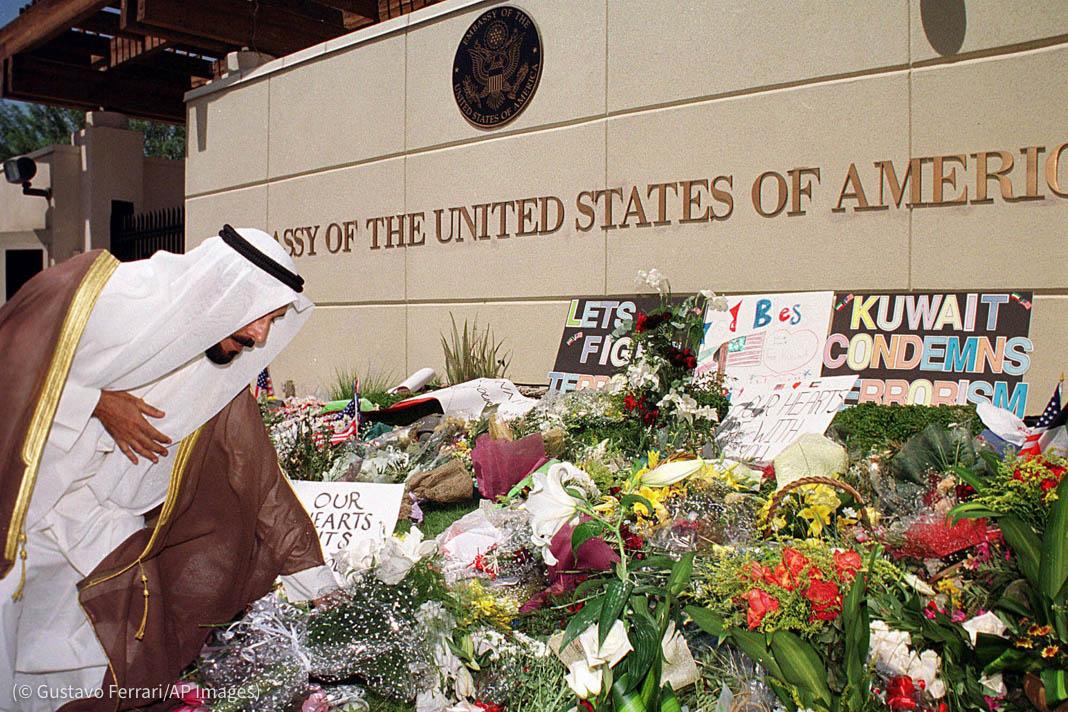 کویت میں امریکی سفارت خانے کے سامنے پھول رکھتے ہوئے ایک شیخ۔ (© Gustavo Ferrari/AP Images)