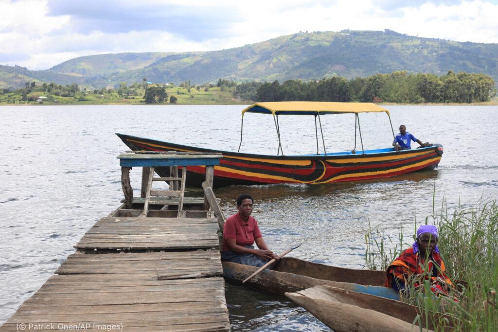 一位老妇人4月份在乌干达本尼奥尼湖(Lake Bunyonyi)布瓦纳岛(Bwama Island)的医疗站接种COVID-19疫苗后与女儿一起离开。(© Patrick Onen/AP Images)
