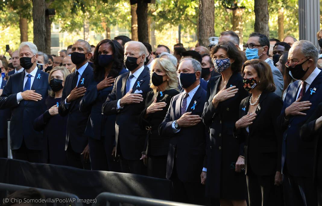 صدر بائیڈن اور امریکہ کی دیگر سیاسی شخصیات اپنے سینوں پر ہاتھ رکھے کھڑے ہیں۔ (© Chip Somodevilla/Pool /AP Images)
