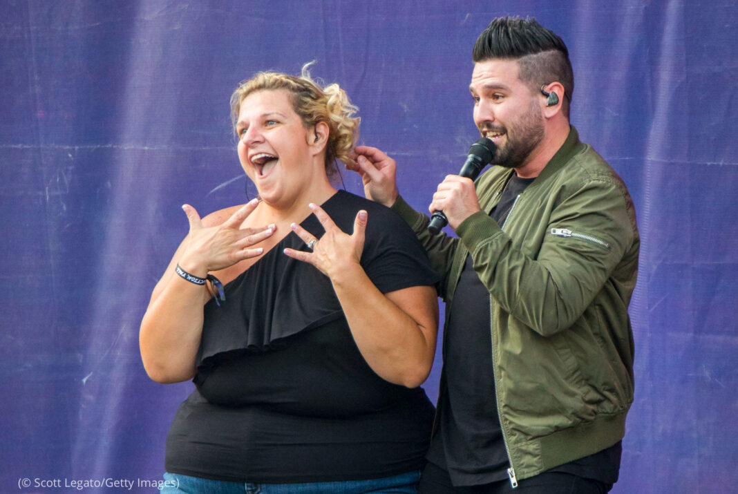 Woman doing sign language with a male singer behind her (© Scott Legato/Getty Images)
