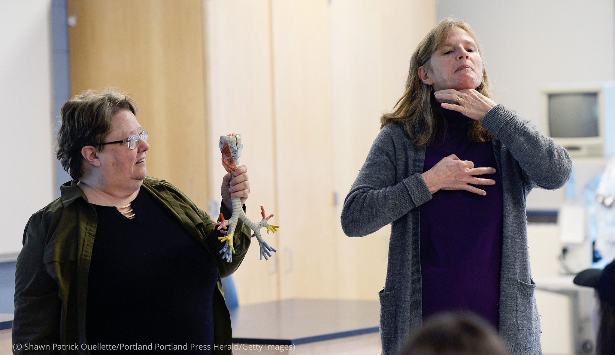 Woman holding model of trachea and bronchi, another woman tracing her windpipe with her hands (© Shawn Patrick Ouellette/Portland Portland Press Herald/Getty Images)