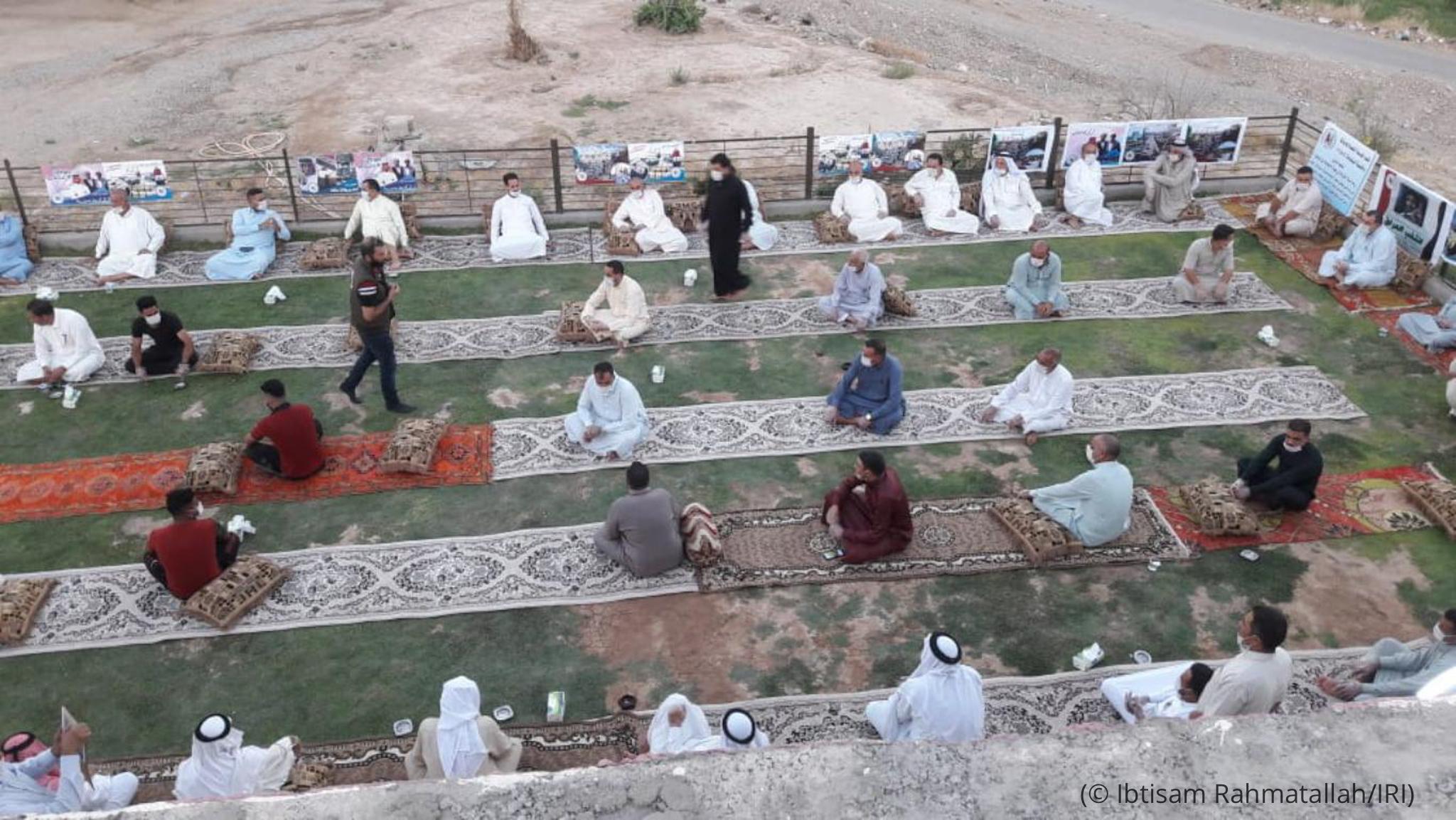 Hombre sentado ante una hilera de alfombras (© Ibtisam Rahmatallah/IRI)