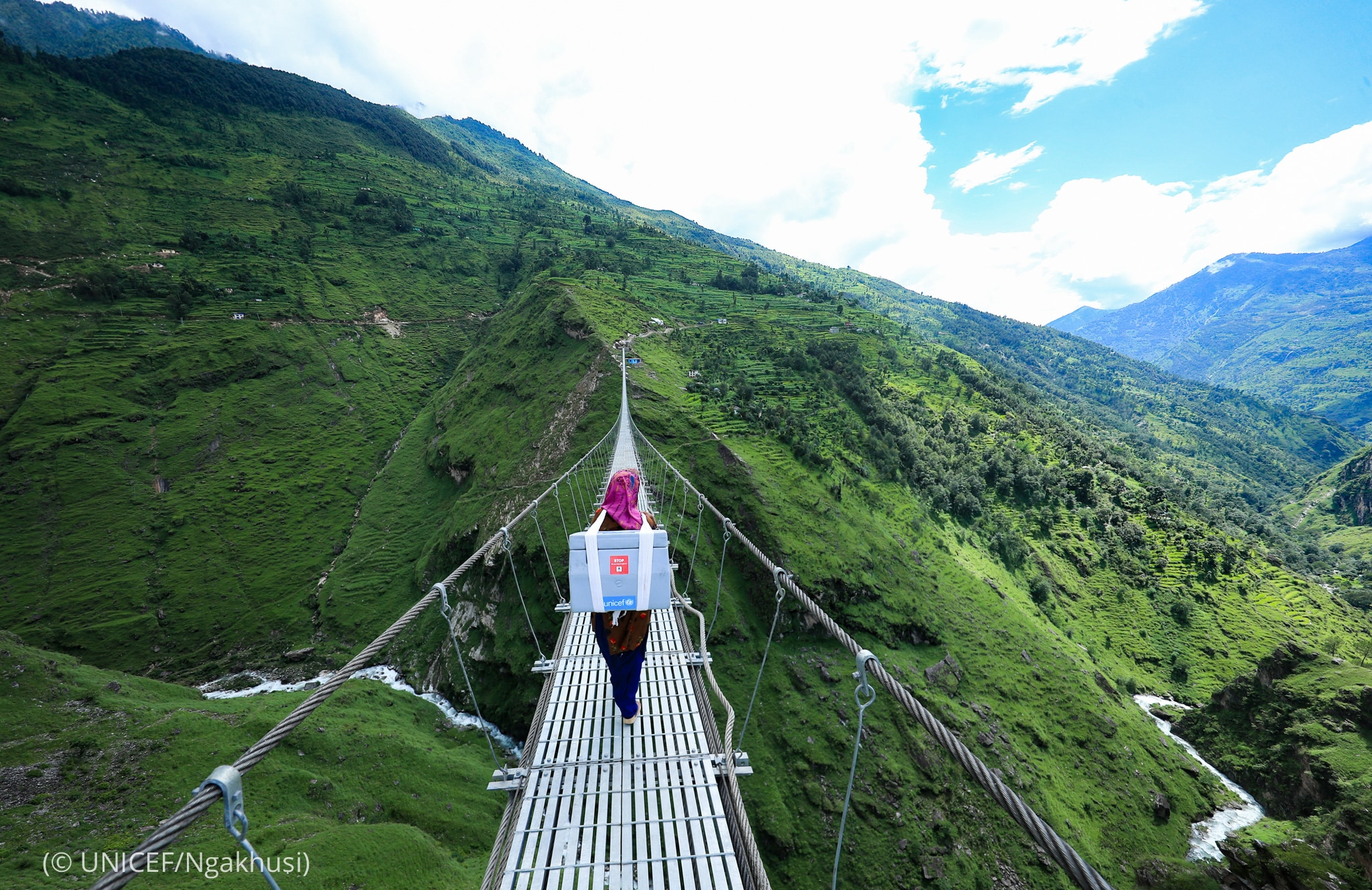 Woman with box strapped to her back walking across narrow bridge in mountains (© UNICEF/Ngakhusi)