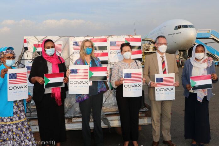 Des gens debout les uns à côté des autres, tenant des posters COVAX, et un avion en arrière-plan (Gouvernement des États-Unis)