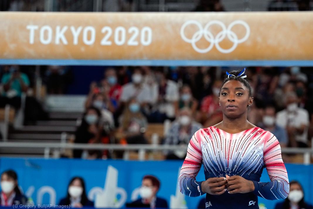 Simone Biles looking at a balance beam (© Gregory Bull/AP Images)