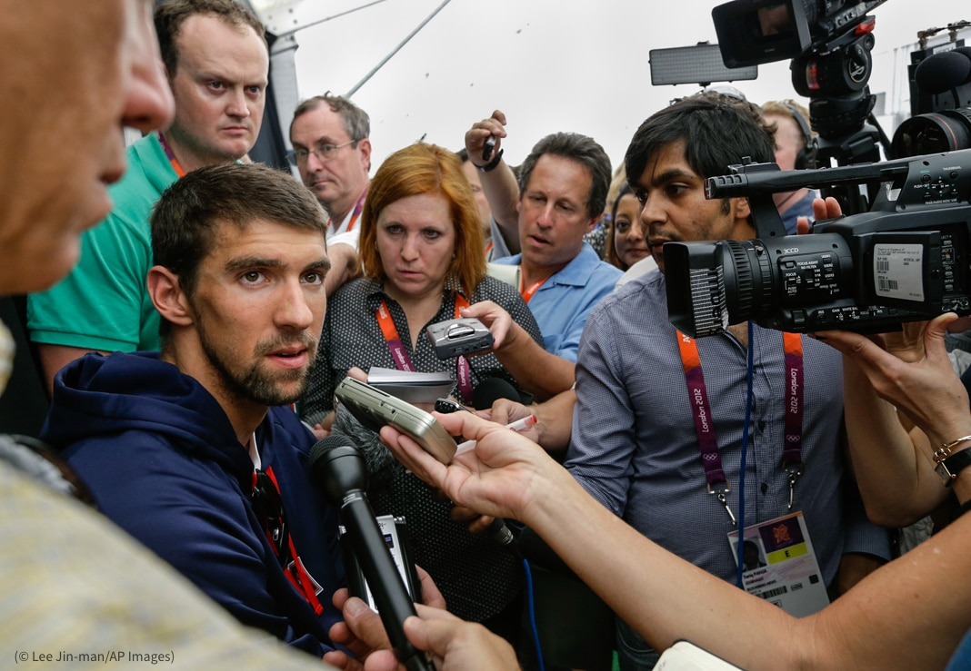 Michael Phelps surrounded by people holding microphones and tape recorders (© Lee Jin-man/AP Images)