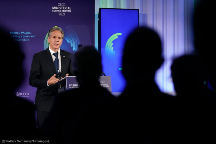 El secretario de Estado de Estados Unidos Antony Blinken habla desde un atril, al frente se ven siluetas de personas (© Patrick Semansky/AP Images)