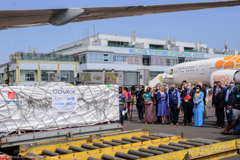 官员们在机场站在飞机附近的货箱旁