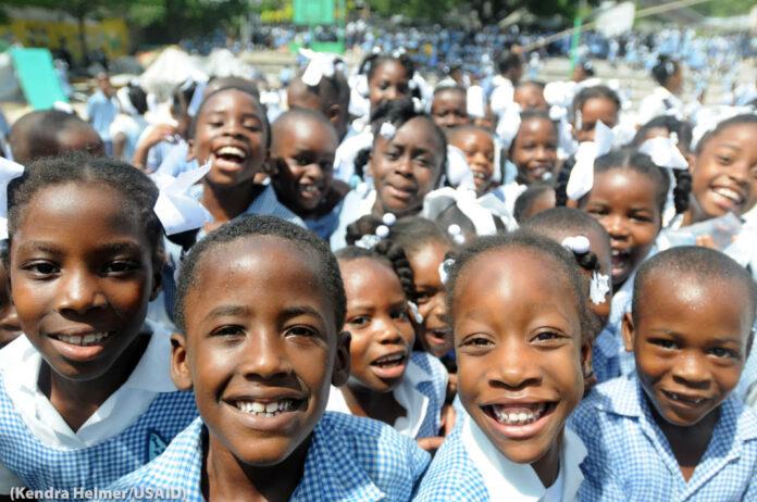 Une foule d'écoliers souriant à l'appareil photo (Kendra Helmer/USAID)