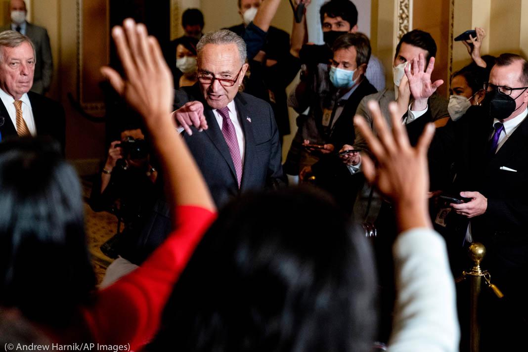 سياسي يشير للصحفيين الذين يرفعون أياديهم لطرح الأسئلة (© Andrew Harnik/AP Images)
