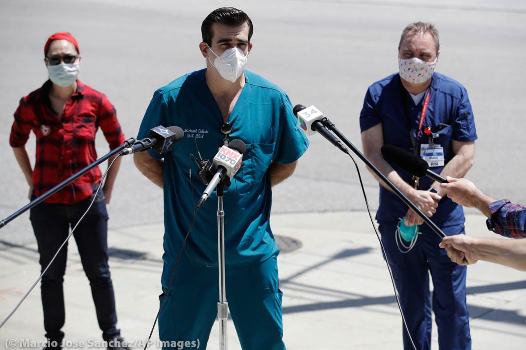 ثلاثة ممرضين واقفون بالقرب من ميكروفونات (© Marcio Jose Sanchez/AP Images)